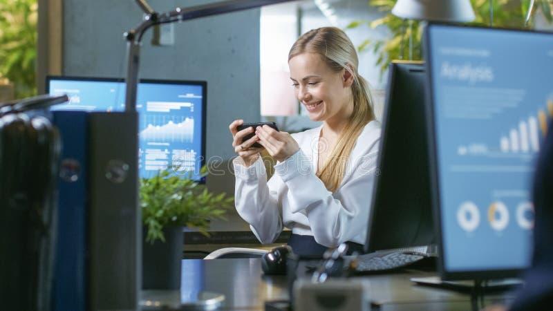 Dans la femme d'affaires attirante Plays Video Games de bureau sur la sa image libre de droits