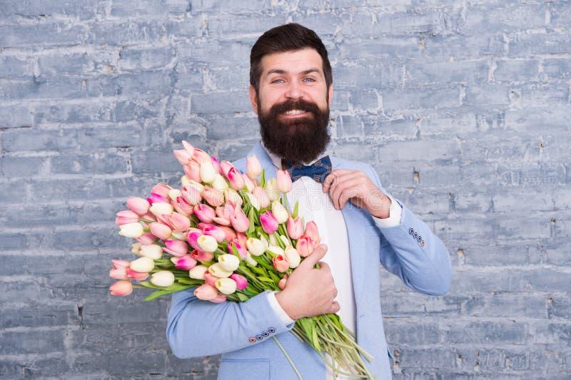 Dans la grande humeur Salutation du ressort 8 mars Amour Vacances internationales Homme barbu avec le bouquet de tulipe de mariag photographie stock