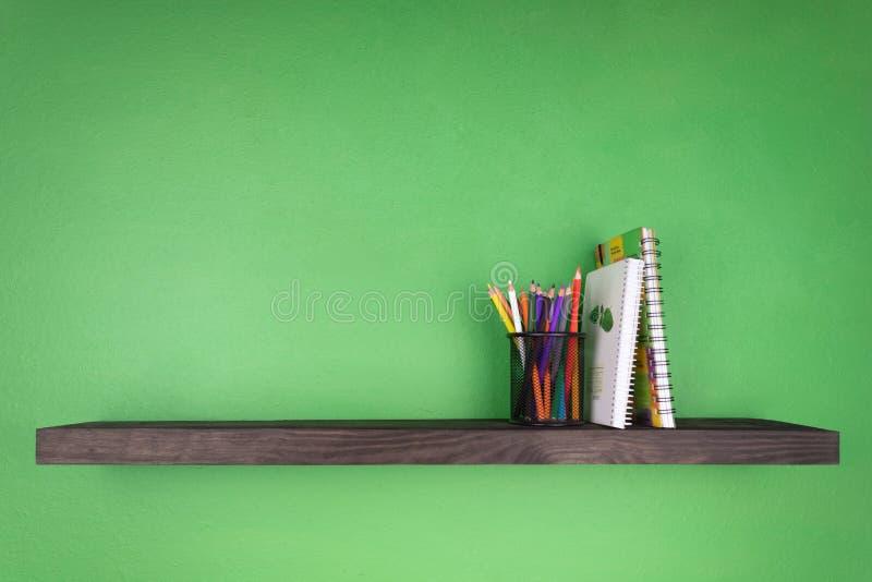 Dans la perspective d'un mur vert une étagère foncée avec la texture du bois sur ce qui est installé un verre avec les crayons co image libre de droits