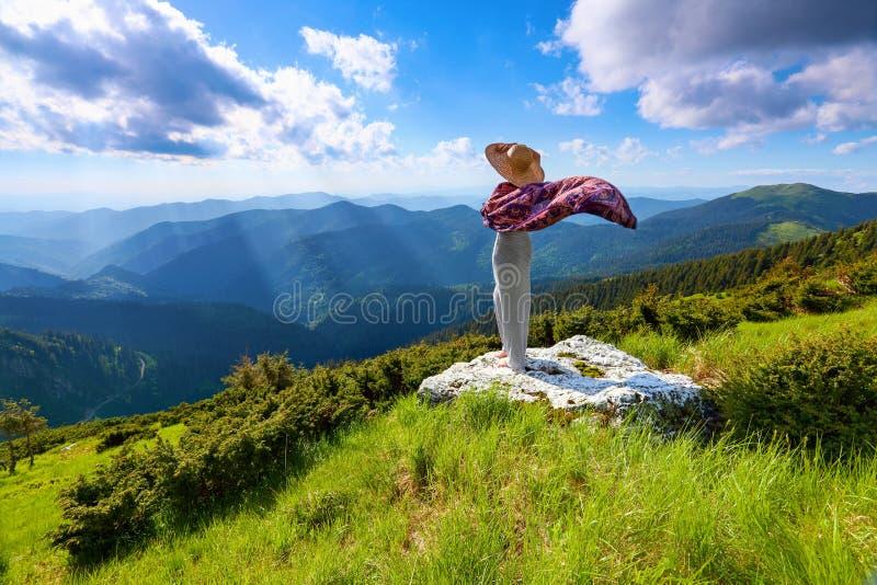Dans la perspective du beau paysage de montagne avec les rayons du soleil et le ciel nuageux la fille reste dans la longue robe,  photos stock
