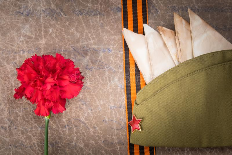 Dans la perspective du vieux papier, de l'oeillet rouge, des enveloppes, du chapeau militaire et du ruban de St George, plan rapp photos libres de droits