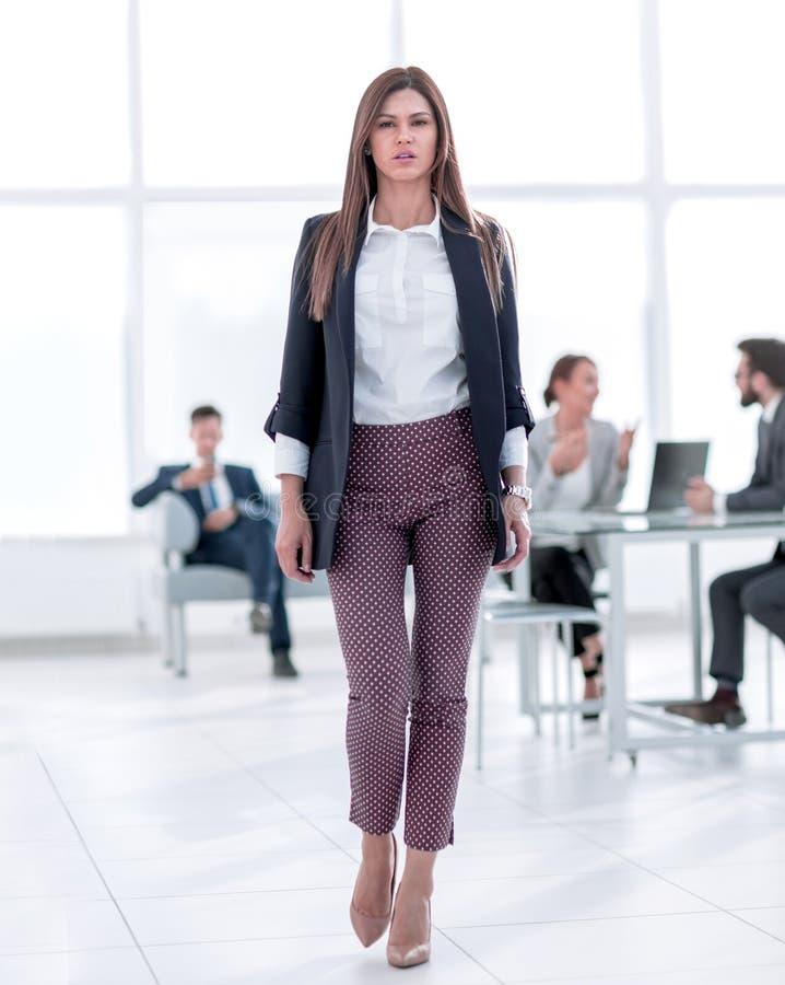 Dans la pleine croissance Jeune femme d'affaires sur le fond du bureau image libre de droits