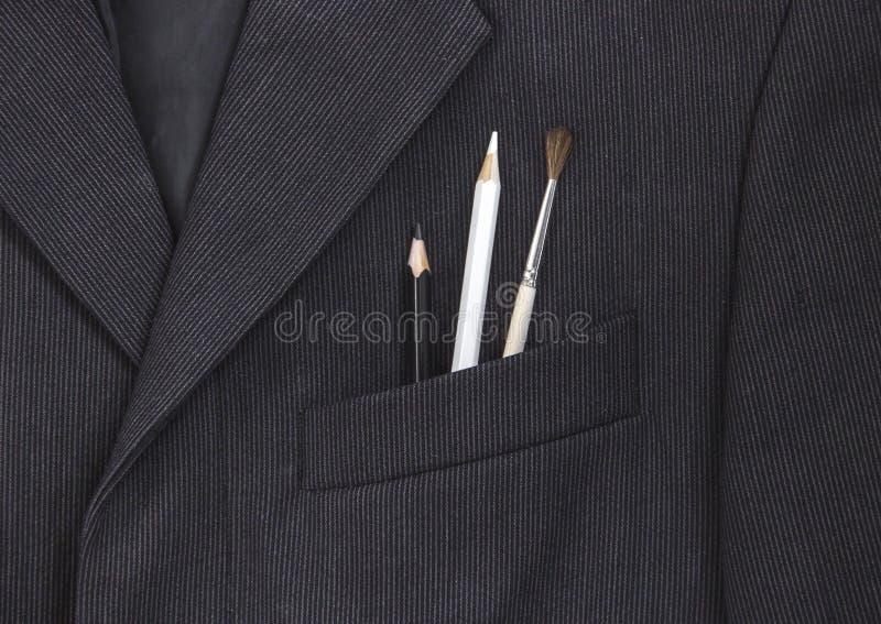 Dans la poche de poitrine d'une veste foncée du ` s d'homme de couleur un crayon et une configuration de brosse dans une bande lé photo stock