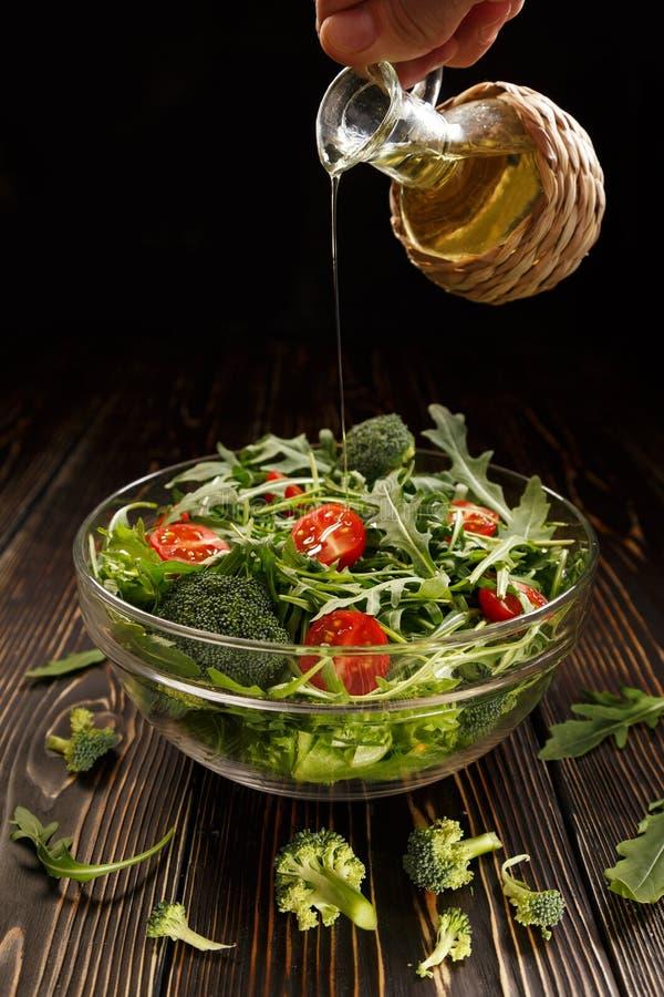 Dans la salade versez l'huile végétale images stock