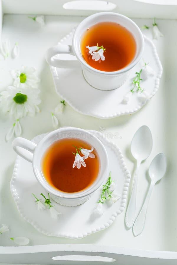 Dans la tasse de thé avec du miel sur la table blanche images stock