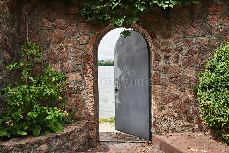 Dans le beau mur en pierre la porte de fer est entrebâillée photographie stock libre de droits