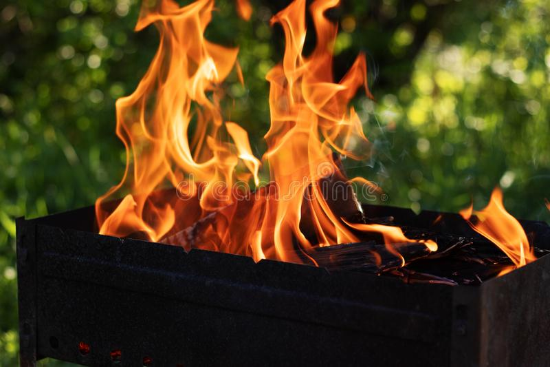Dans le bois de chauffage de brûlure de gril de barbecue photographie stock