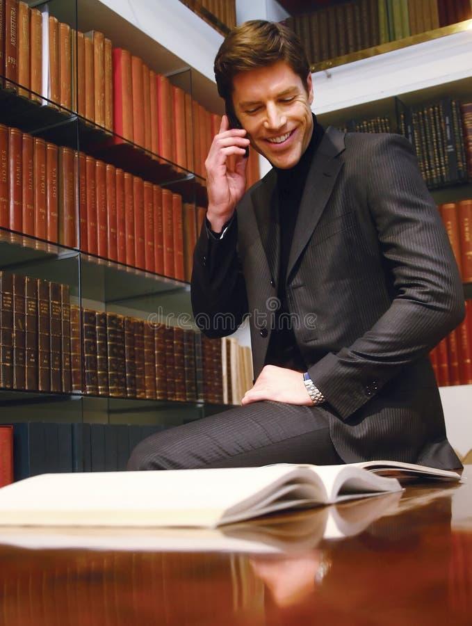 Dans le bureau regardant le livre et parlant au téléphone photo stock