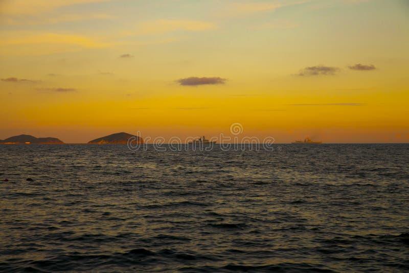 Dans le coucher du soleil les bateaux de la Marine puissants se dirigeaient pour le port images stock