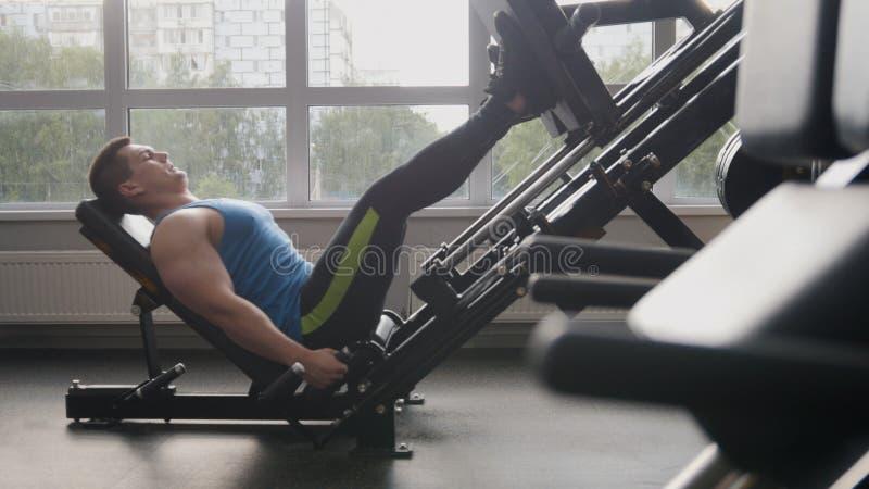 Dans le gymnase - homme musculaire s'exerçant sur la machine de presse de jambe photographie stock