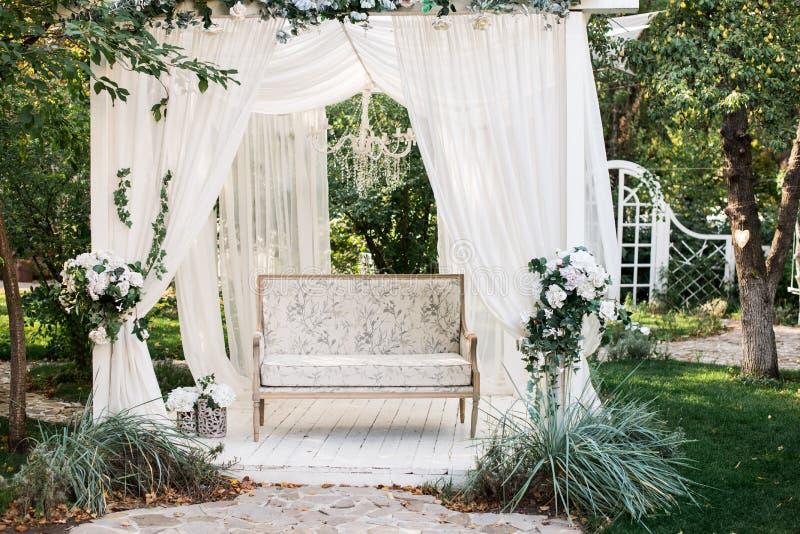 Dans le jardin il y a un podium sur lequel un beau sofa blanc dans le style de la Provence ou rustique Au-dessus du sofa est une  photographie stock