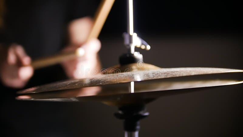 Dans le premier plan il y a les cymbales de tambour Dans le fond il y a les mains qui tiennent le pilon images libres de droits