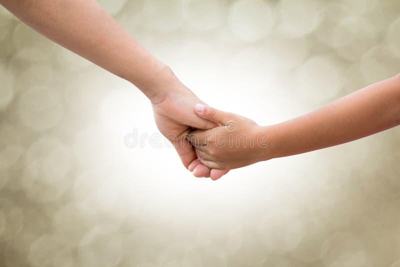 Dans les mains des parents et des enfants sur un fond brouillez le bokeh Mère arrêtée pour le ton de sépia de style de soin de bé photographie stock