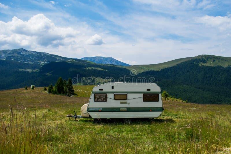 Dans les montagnes, avec une caravane Un paysage superbe de montagne Herbe verte et un ciel bleu avec des nuages photographie stock