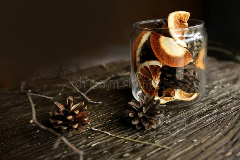 Dans un pot en verre, des cônes de pin et des oranges sèches photographie stock libre de droits