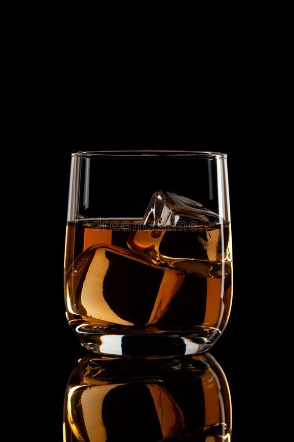 Dans un verre d'eau-de-vie fine avec de la glace sur un fond noir photographie stock