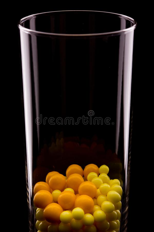 Dans un verre transparent il y a les comprimés ronds jaunes et rouges Un verre est reflété dans le noir Fond foncé photographie stock libre de droits