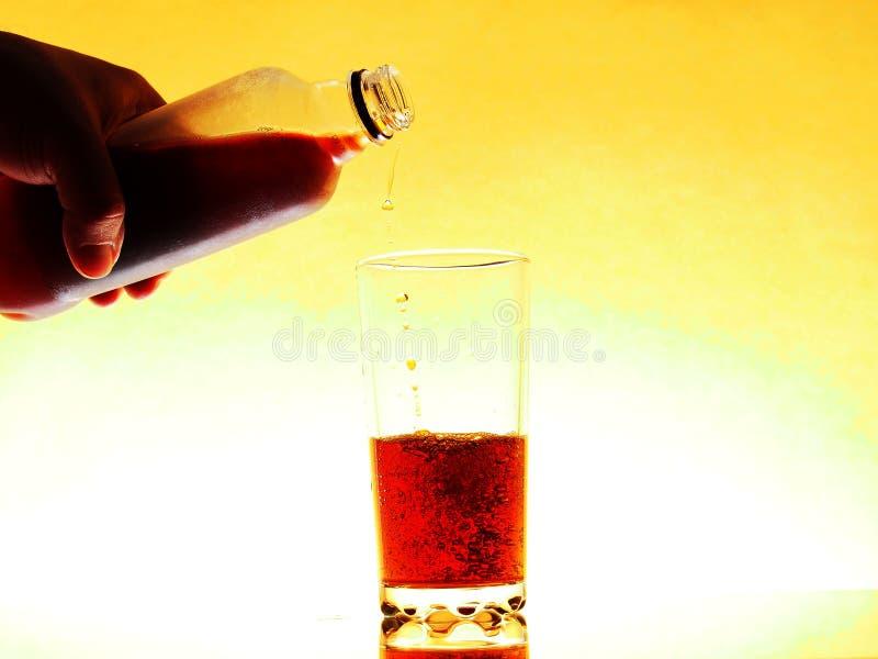 Dans un verre transparent rempli d'une boisson gazeuse foncée Cola, bière, cocktail images libres de droits