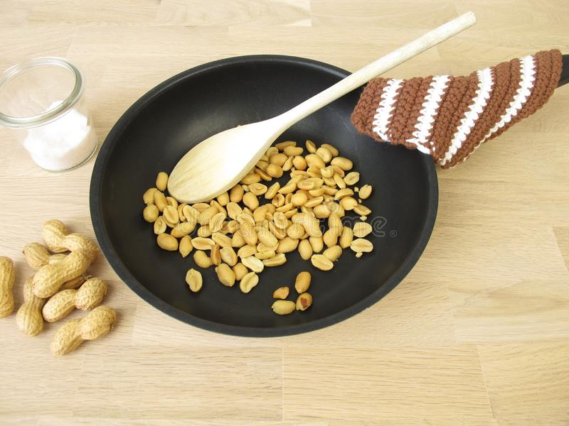 Dans une casserole arachides rôties image libre de droits