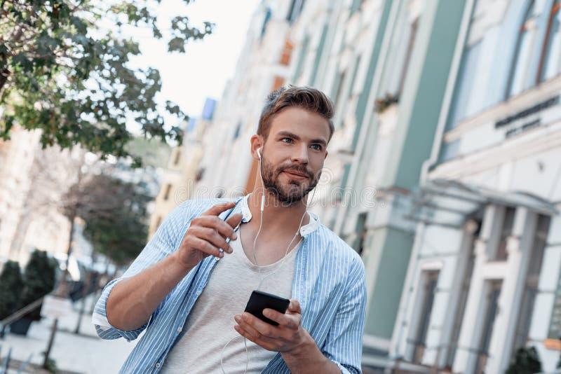 Dans une grande humeur Le jeune homme écoute la musique par l'intermédiaire des écouteurs tout en marchant autour de la ville photographie stock libre de droits