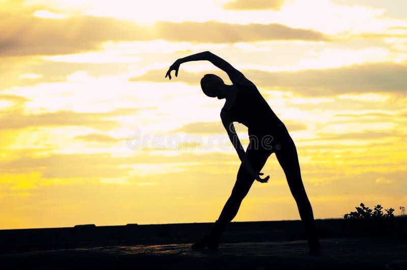 dansa över yoga för silhouettesolnedgångkvinna arkivbilder