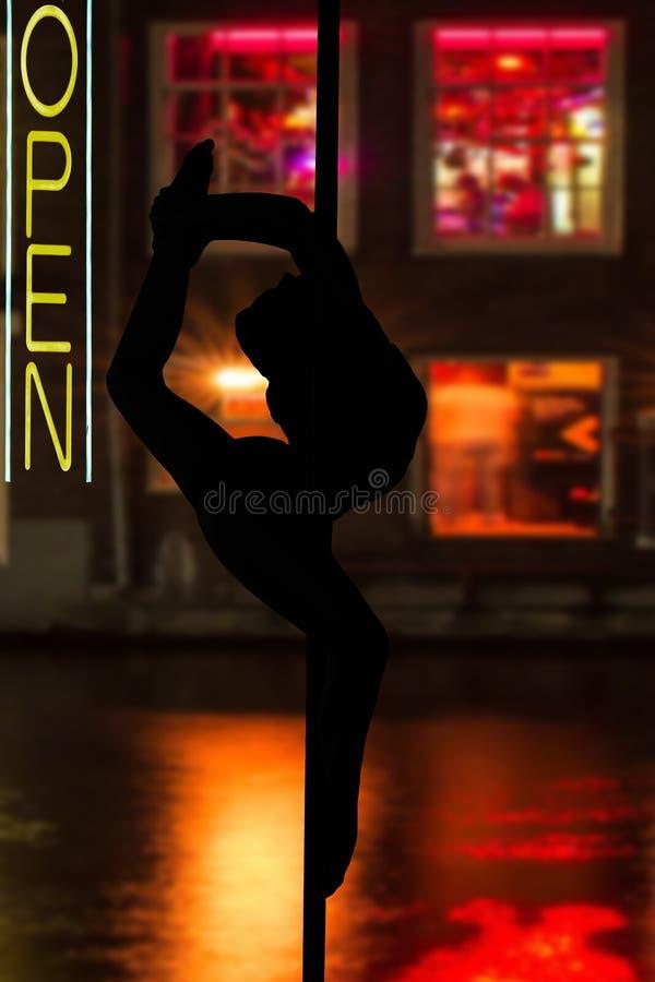 Dansa den eleganta unga flickan som framme hänger i en danspol av fönster med rött ljus och, öppna tecknet arkivbilder