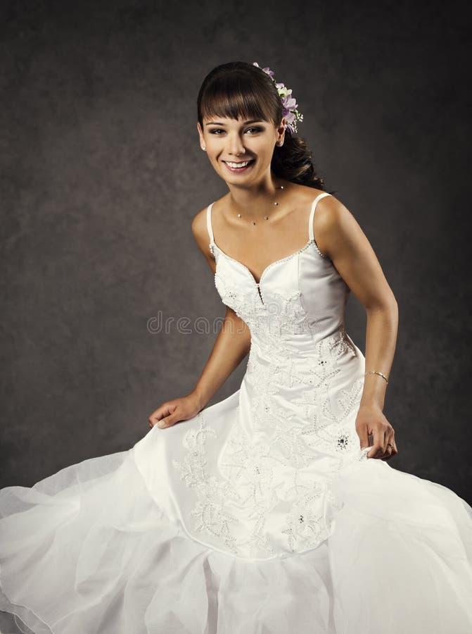 Dansa den roliga bruden i bröllopsklänning, emotionell brud- stående royaltyfria foton