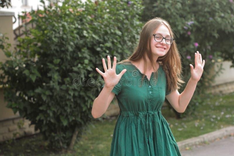 Dansa den tonåriga ålderflickan i exponeringsglas och grön klänning och att ha gyckel Sommar utomhus- bakgrund kopiera avst?nd royaltyfri foto