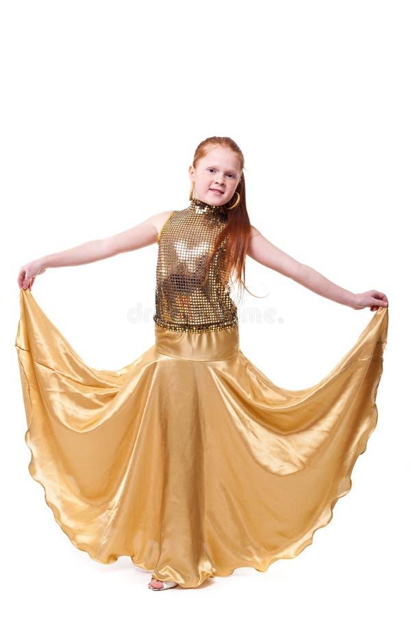 Dansa lycklig liten flicka i guld- klänning fotografering för bildbyråer