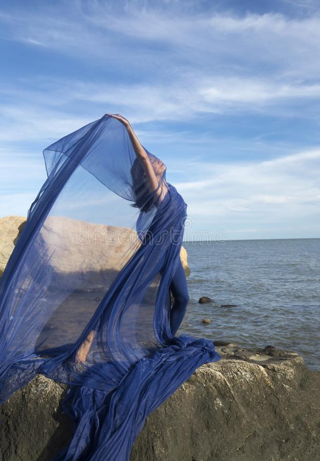 Dansare för ung kvinna som kastar blått tyg på en Connecticut strand royaltyfri bild