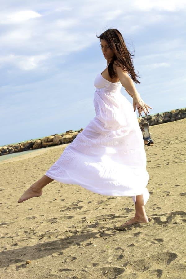 Dansare som poserar med den vita klänningen på stranden royaltyfri foto