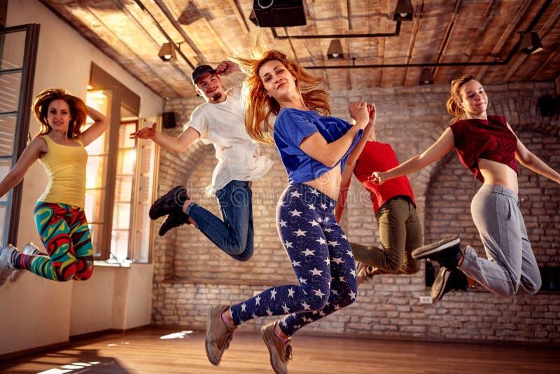 Dansarelag - dansarevänner som hoppar under musik arkivbilder