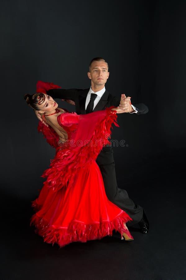 Dansbalsalpar i röd klänningdans poserar isolerat på svart bakgrund sinnliga yrkesmässiga dansare som dansar walz, tango som är l royaltyfri foto