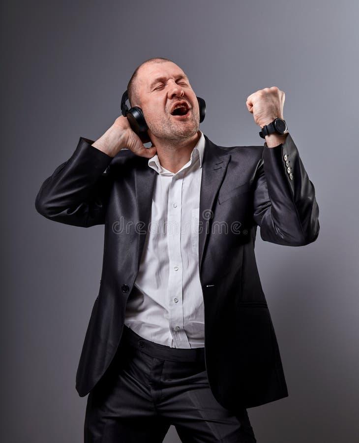Danse émotive heureuse et homme chauve chanteur écoutant la musique dans l'écouteur sans fil sur le fond gris-foncé closeup photo stock