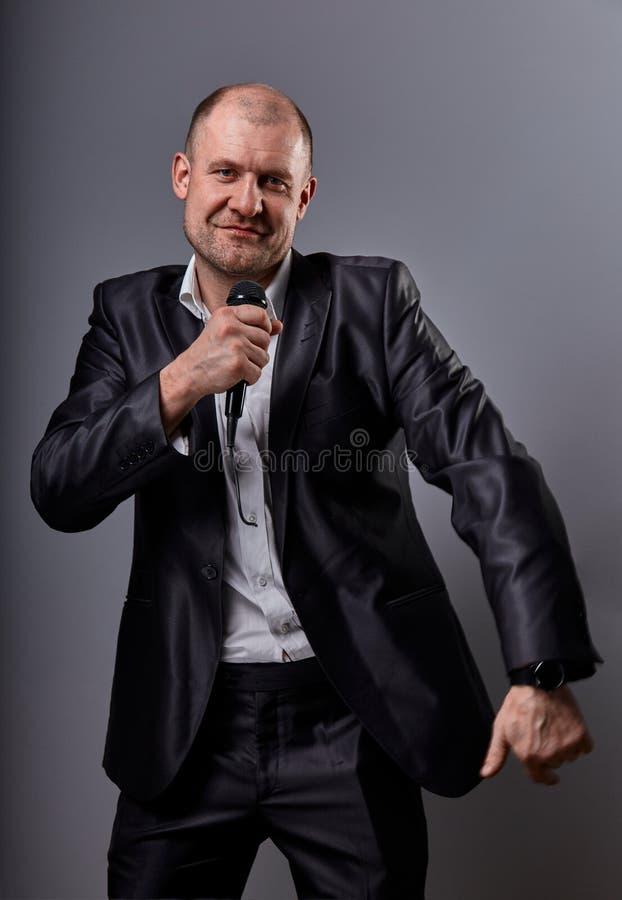 Danse émotive heureuse et homme chauve chanteur écoutant la musique dans l'écouteur sans fil sur le fond gris-foncé closeup image stock