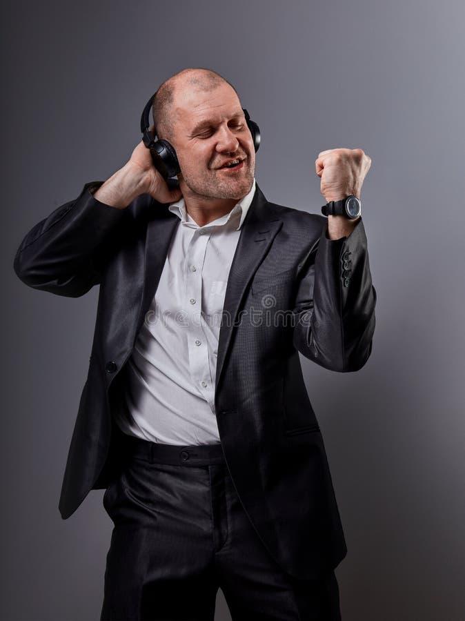 Danse émotive heureuse et homme chauve chanteur écoutant la musique dans l'écouteur sans fil sur le fond gris-foncé closeup photo libre de droits