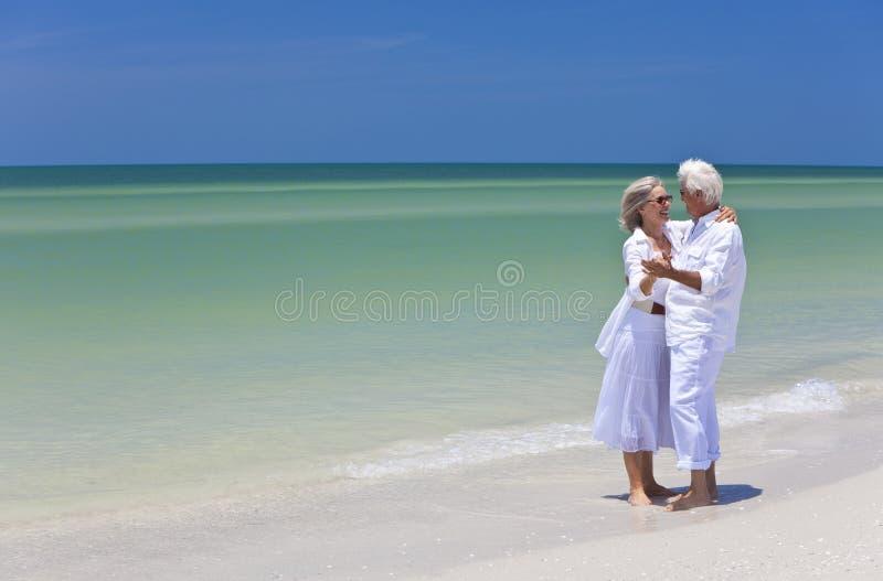 Danse aînée heureuse de couples sur la plage tropicale image stock