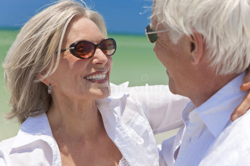 Danse aînée heureuse de couples sur une plage tropicale photographie stock