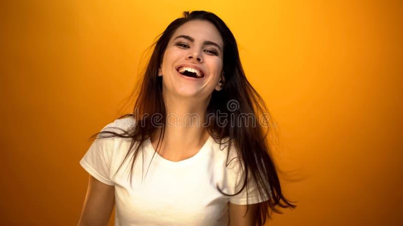 Danse attrayante de fille et sincèrement sourire à la caméra, appréciant le moment photographie stock libre de droits
