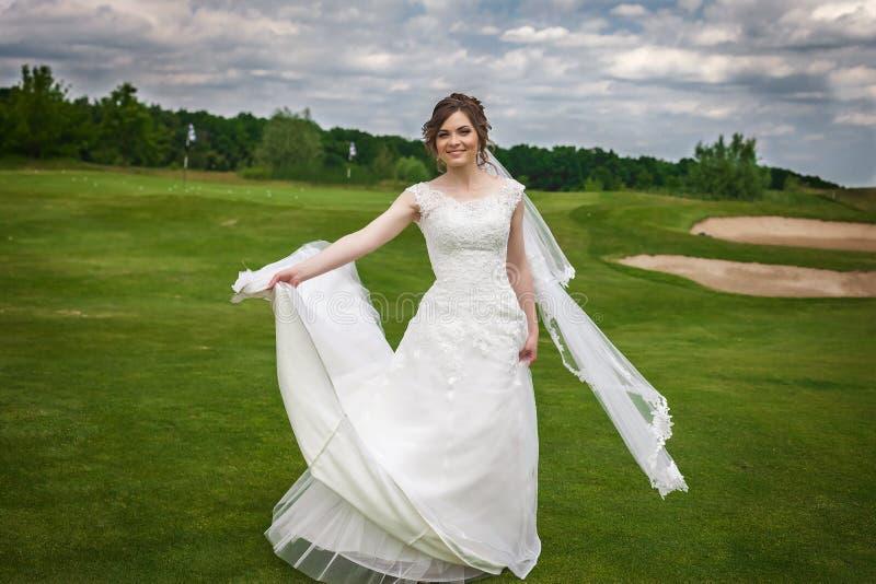 Danse attrayante de jeune mariée sur le terrain de golf vert image libre de droits