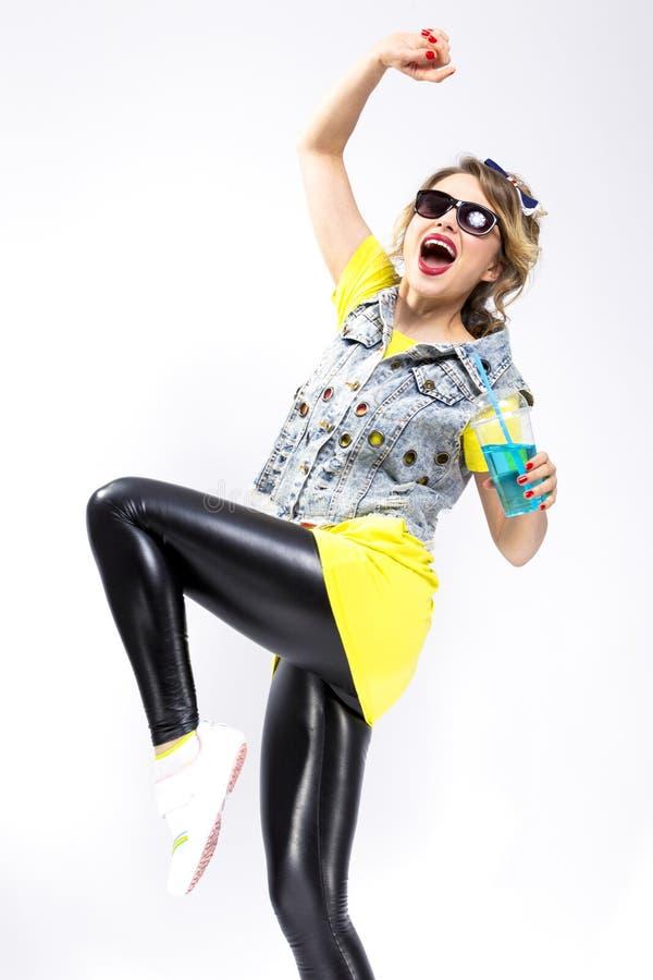 Danse blonde caucasienne de fille avec la tasse du cocktail bleu Gilet et lunettes de soleil de port de denim photo stock