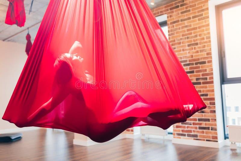Danse créative de performig de jeune femme utilisant l'hamac rouge comme équipement de suspension photos libres de droits