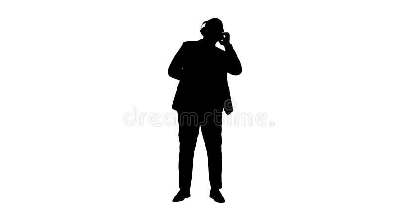 Danse d'homme d'affaires de noir de silhouette en musique dans des écouteurs photographie stock