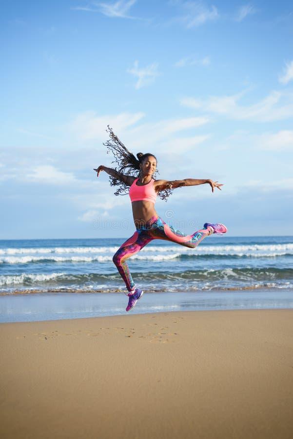 Danse de femme de forme physique et sauter à la plage photographie stock