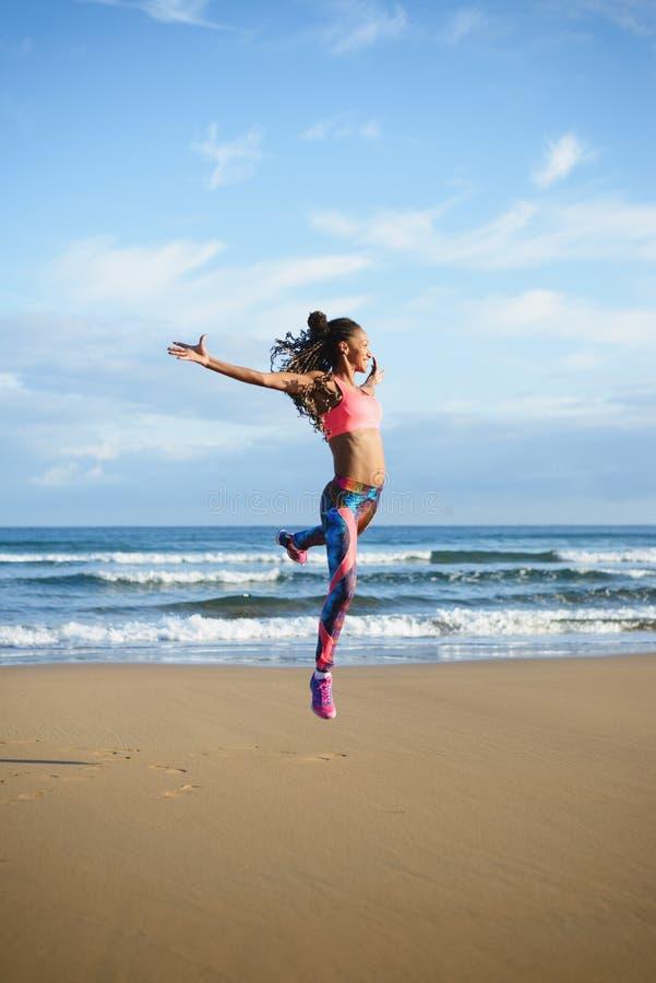 Danse de femme de forme physique et sauter à la plage photos libres de droits