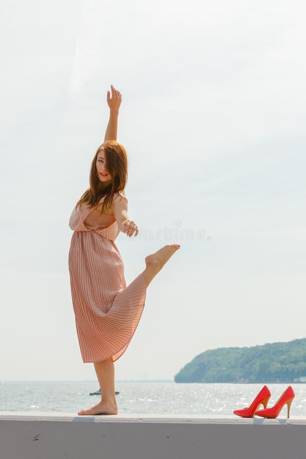 Danse de femme portant la longue robe rose-clair photographie stock