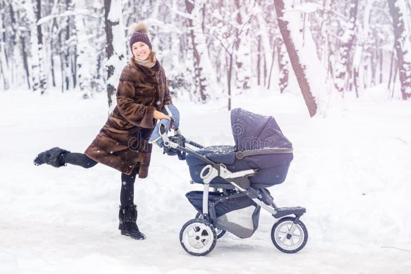 Danse de femme tandis que promenade d'hiver avec une poussette photographie stock libre de droits
