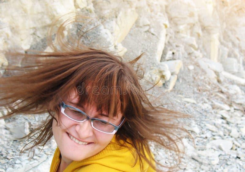 Danse de fille dans les roches avec les poils de ondulation photo stock