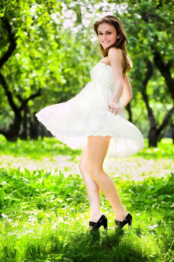 Danse de fille de sourire dans la robe blanche photographie stock libre de droits