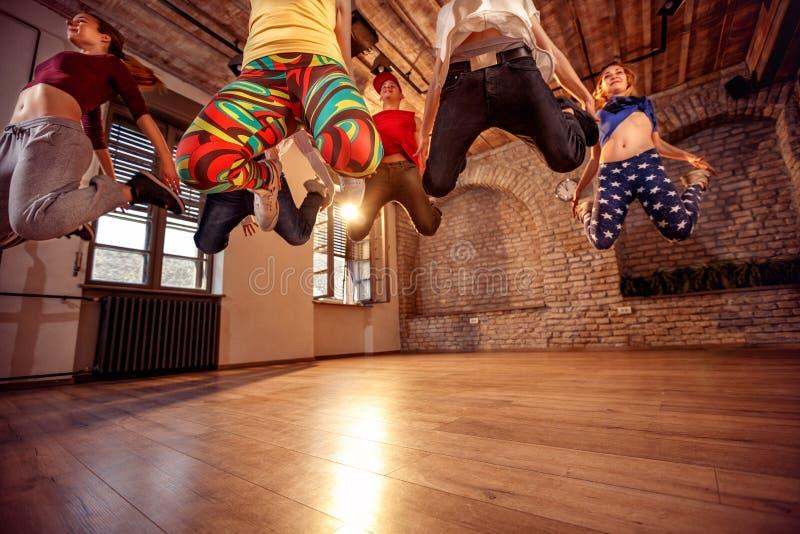Danse de danse moderne de pratique en matière de groupe dans le saut photographie stock